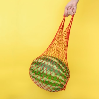 黄色の背景にスイカとメッシュショップバッグ。廃棄物ゼロ、環境に優しいプラスチックフリーのコンセプト。健康的なきれいな食事とデトックスコンセプト