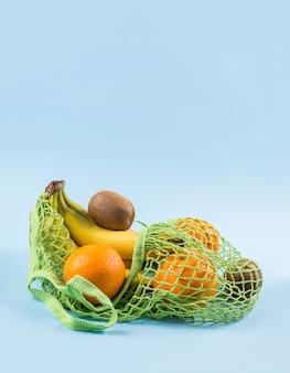 Mesh shopping bag with bananas, oranges and kiwi