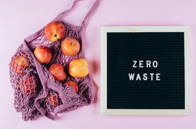 Mesh shopping bag with fruits and letters black board with text zero waste on pink.