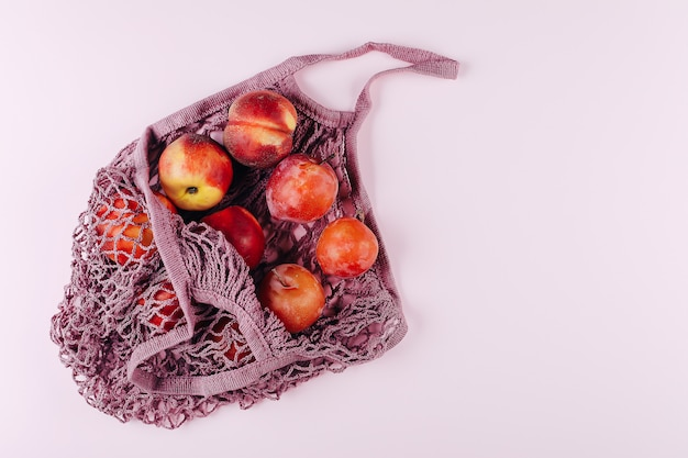 Mesh shopping bag with fruits plims and peach on pink. top view, flat lay, copy space.