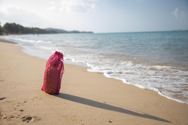 Сетка хозяйственная сумка с фруктами стоит на песчаном пляже моря в солнечный день экология