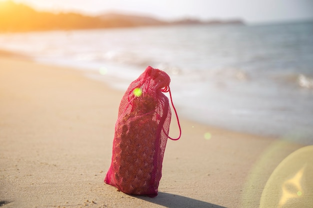 Mesh shopping bag with fruits stands on the sandy beach of the sea on a sunny day.. ecology of the oceans concept