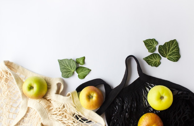 Mesh shopping bag with green apples on white background.