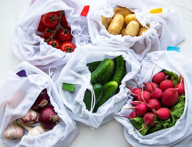 大理石の背景に有機野菜のメッシュショッピングバッグ。フラットレイ、上面図。ゼロウェイスト、プラスチックフリーのコンセプト。夏の果物。