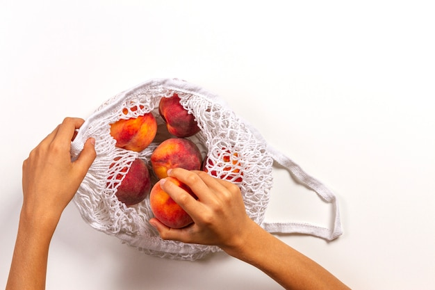 Mesh shopping bag with peaches on white background