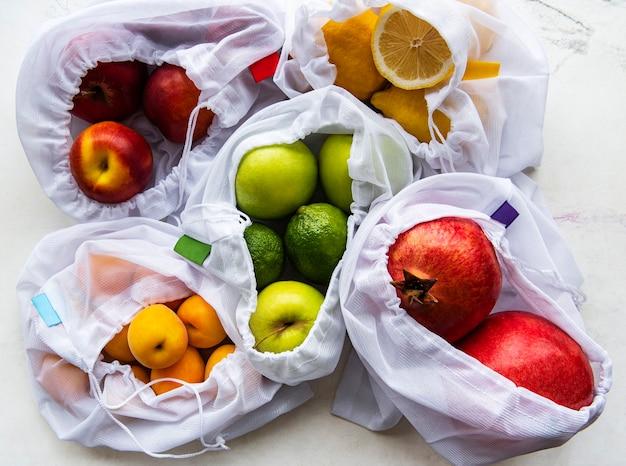 Сетчатые хозяйственные сумки с органическими фруктами на мраморной поверхности