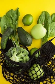 Сетка для покупок черная сумка с зелеными фруктами и овощами на желтом