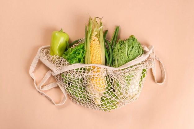Mesh string bag with green vegetables on a beige background.
