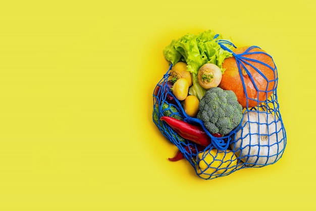 Mesh textile bag full of mixed vegetables. healthy food and zero waste concept.