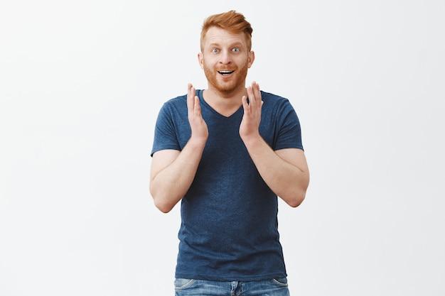 美しい景色に魅了されました。青いtシャツに剛毛を持った、驚いて幸せそうな赤毛の男性。灰色の壁に印象を与えながら、手のひらを上げて喜んで興奮しています。