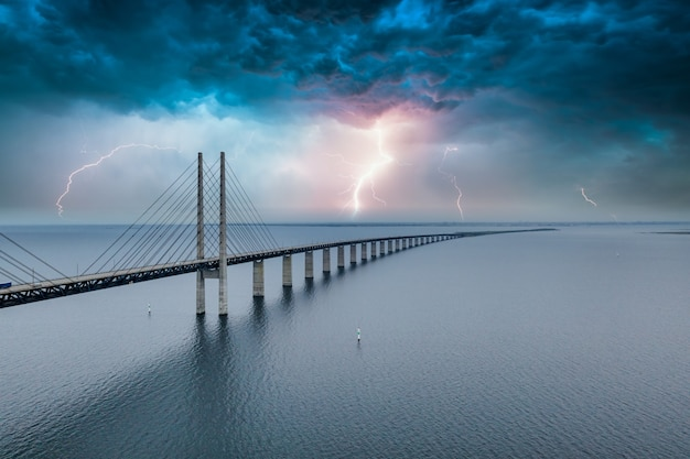 Mesmerizing aerial view of the bridge between denmark and sweden under the sky with lightning