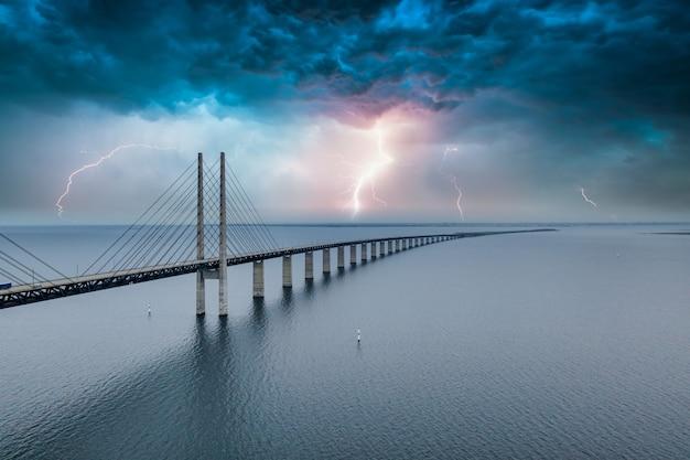 稲妻の空の下でデンマークとスウェーデンの間の橋の魅惑的な空中写真