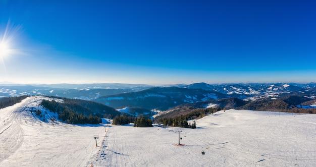 山と雪の丘に囲まれた絵のように美しい場所にあり、青い空の凍るような冬の夜にある魅惑的なケーブルカー。ヨーロッパ諸国における冬の観光の概念。