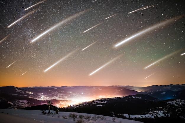 凍るような冬の夜の高い山脈の中に、輝く村の星空を背景にした流れ星の魅惑的な風景があります。 ufoの概念神秘主義と異常現象