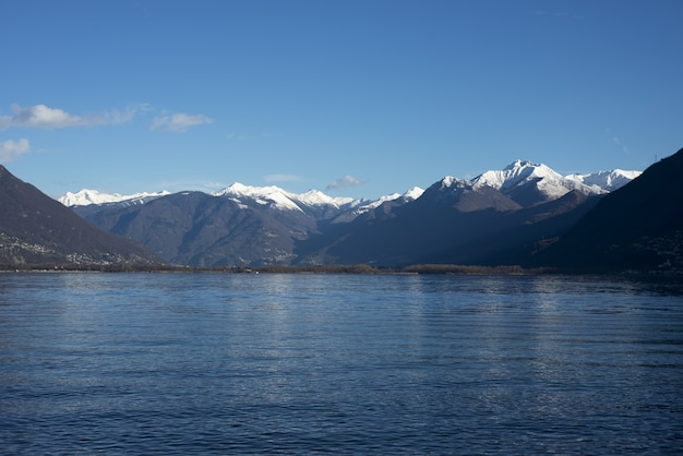 昼間の壮大な山々に対する湖の魅惑的な写真
