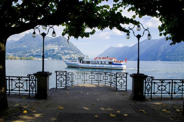 スイス、ルガーノの霧深い山々に対する帆船の魅惑的な写真