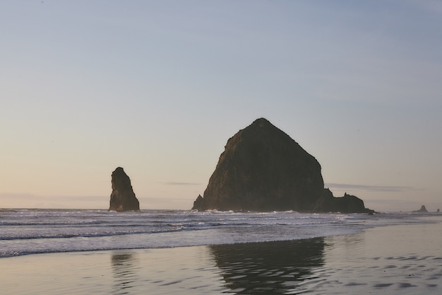 오레곤 주 태평양에있는 건초 더미 바위에서 일몰의 매혹적인 풍경