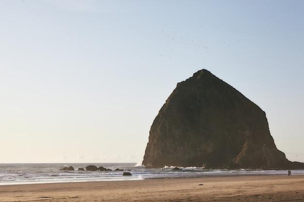 Завораживающие пейзажи заката на скале haystack rock в тихом океане, штат орегон