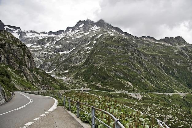 흐린 하늘 아래 산들 사이의 아름다운 길의 매혹적인 풍경