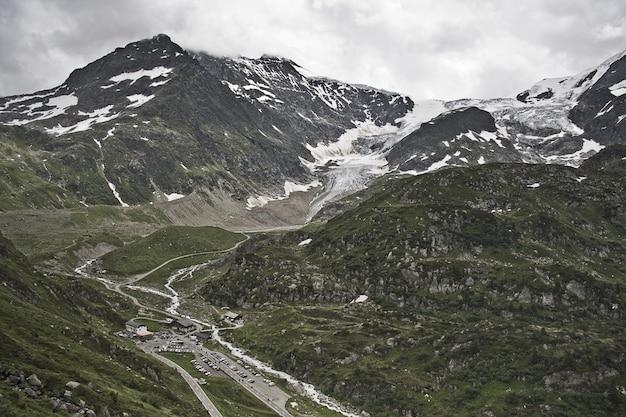 曇り空の下、雪をかぶった美しい山々の魅惑的な風景