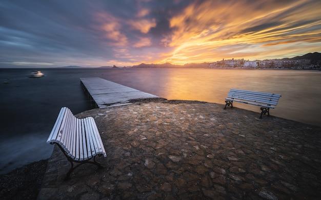 風光明媚な夕日の前景に木製の桟橋とベンチがある魅惑的な海の景色