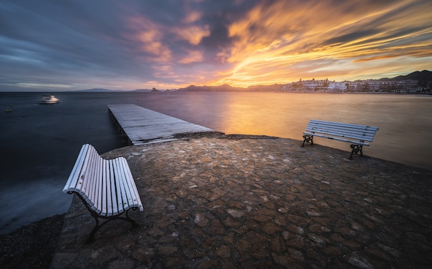 Mesmerizing seascape with a wooden pier and benches on the foreground at the scenic sunset
