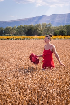 Mesmerizing shot of an attractive female in a red dress posing at front in a wheat field