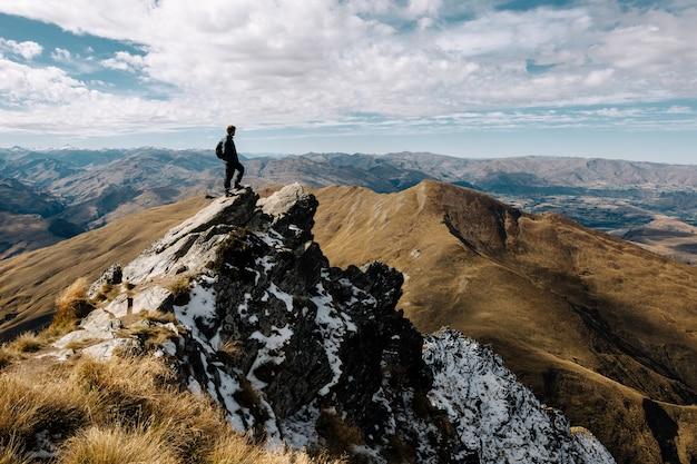 Завораживающий снимок мужчины, стоящего на вершине горы днем