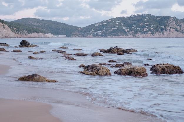 曇り空の下の岩の多い海岸の魅惑的なショット