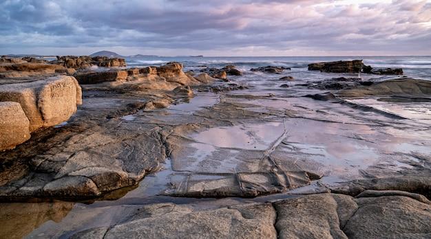 석양에 바위 해안의 매혹적인 샷