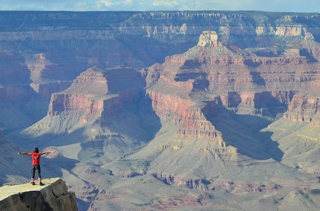アリゾナ州サウスリムからコロラド州のグランドキャニオンを見つめる観光客の魅惑的なショット