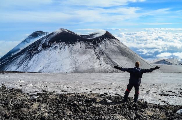 Завораживающий снимок туриста, посещающего вулкан этна на сицилии, италия