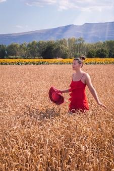 밀밭 앞에서 포즈를 취하는 빨간 드레스를 입은 매력적인 여성의 매혹적인 샷