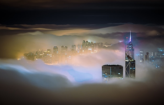 Mesmerizing shot of the skyscrapers of a city covered in mist at night