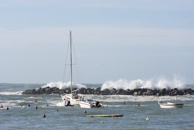 Mesmerizing shot of the waves behind floating boats at daytime