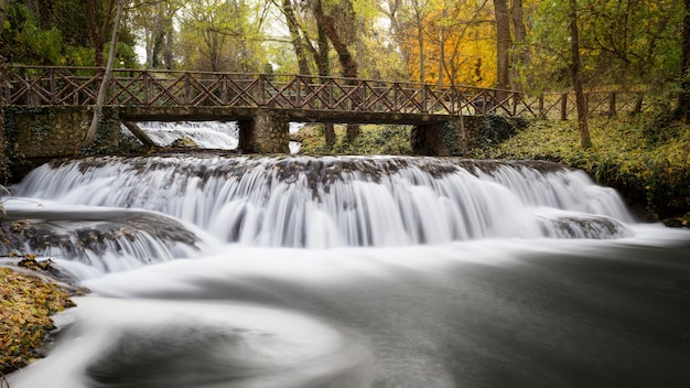 Mesmerizing view of a bridge over the beautiful waterfall in the middle of a forest