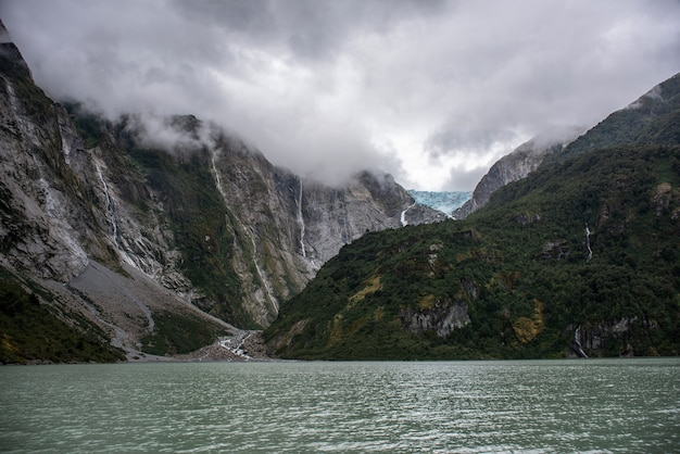 Vista affascinante dell'oceano calmo e delle montagne rocciose con una cascata