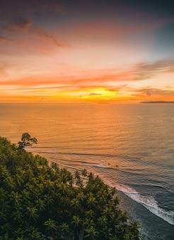 Vista affascinante dell'oceano calmo e degli alberi sulla riva durante il tramonto in indonesia