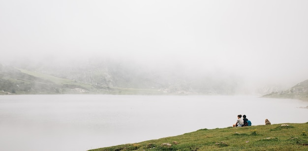 Mesmerizing view of the foggy lake with people sitting