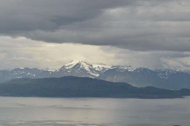 Vista affascinante delle montagne coperte di neve dietro il lago in una giornata uggiosa
