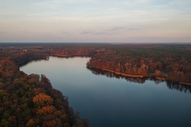 Завораживающий вид на спокойное озеро в окружении разноцветных осенних деревьев.