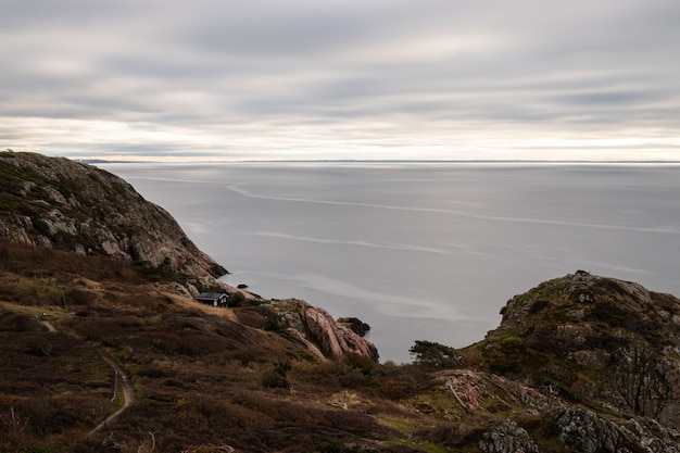 Завораживающий вид на спокойный океан в окружении скалистых гор в пасмурный день