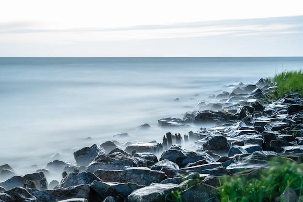 맑은 하늘 아래 해안선에 돌이있는 잔잔한 바다의 매혹적인 전망