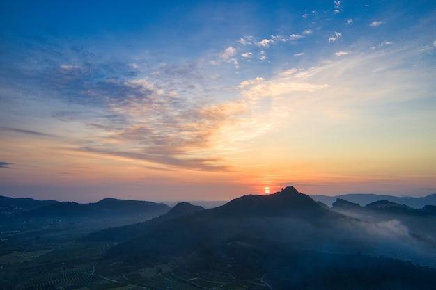 언덕과 산 너머 오렌지 일몰의 매혹적인 전망