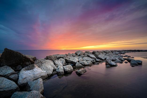 海の石に沈む夕日の魅惑的な景色