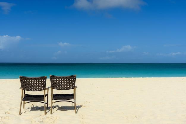 海岸に2つの椅子があり、ビーチと海の魅惑的な景色