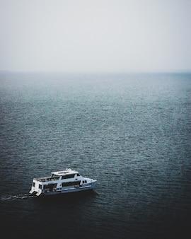 안개가 자욱한 날에 잔잔한 바다에서 보트의 매혹적인 전망