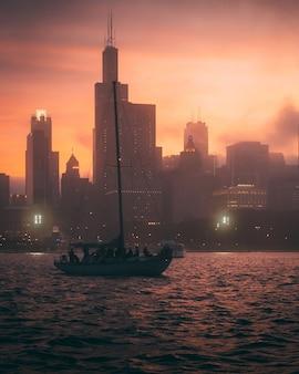 Завораживающий вид на лодку в океане и силуэты высоких зданий на закате.