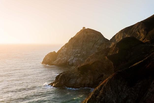 Завораживающий вид на спокойный океан и скалы на берегу под голубым небом во время заката.