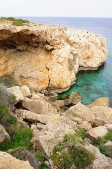 青い空の下の澄んだ海の近くの崖の魅惑的な景色